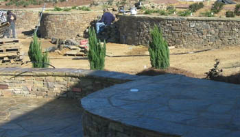 Stone landscape retaining wall at home in Jackson, MS being installed by Ambiance Landscape.