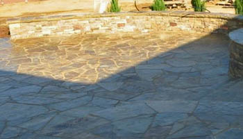 Custom stone patio with seating wall created by Ambiance Landscape in Brandon, MS.
